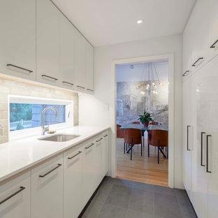 Aménagement d'une cuisine parallèle contemporaine avec un évier encastré, un placard à porte plane, des portes de placard blanches, une crédence grise, un plan de travail en béton, un électroménager blanc, un sol noir, un plan de travail jaune et un sol en ardoise.
