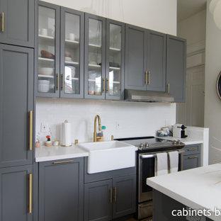 Inspiration för små moderna linjära vitt kök och matrum, med en rustik diskho, luckor med infälld panel, grå skåp, marmorbänkskiva, vitt stänkskydd, stänkskydd i keramik, integrerade vitvaror, laminatgolv, en köksö och brunt golv