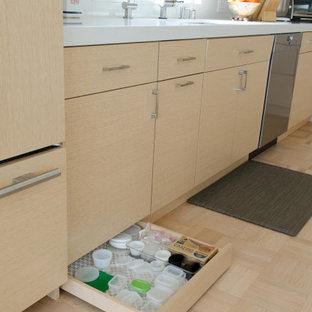Inredning av ett modernt mellanstort vit vitt kök, med en undermonterad diskho, släta luckor, skåp i ljust trä, bänkskiva i kvarts, vitt stänkskydd, integrerade vitvaror, ljust trägolv, en halv köksö och gult golv