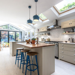 Photo of a classic kitchen in London with flat-panel cabinets, grey cabinets, white splashback, metro tiled splashback, stainless steel appliances, light hardwood flooring and an island.