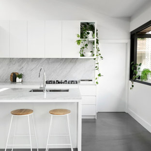 Photo of a contemporary galley kitchen in Melbourne with an undermount sink, flat-panel cabinets, white cabinets, grey splashback, concrete floors, with island, grey floor and white benchtop.