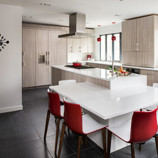 Mid-sized modern kitchen designs - Mid-sized minimalist galley porcelain floor and black floor kitchen photo in New York with flat-panel cabinets, solid surface countertops, paneled appliances, an island, light wood cabinets and an undermount sink