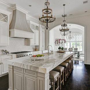 Immagine di una cucina parallela tradizionale chiusa con lavello sottopiano, ante con bugna sagomata, ante bianche, paraspruzzi bianco, elettrodomestici in acciaio inossidabile, parquet scuro, isola e pavimento marrone