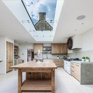 Foto på ett lantligt grå u-kök, med skåp i mellenmörkt trä, bänkskiva i betong, kalkstensgolv, en köksö och beiget golv