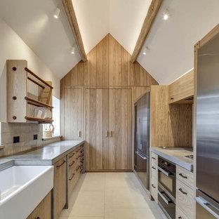 Удачное сочетание для дизайна помещения: параллельная кухня в стиле кантри с раковиной в стиле кантри, плоскими фасадами, светлыми деревянными фасадами, столешницей из бетона, техникой из нержавеющей стали, полом из известняка и бежевым полом без острова - самое интересное для вас