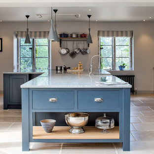 Inspiration for a large traditional kitchen/diner in Wiltshire with a belfast sink, blue cabinets, an island, beige floors, grey worktops, integrated appliances, limestone flooring, shaker cabinets and granite worktops.