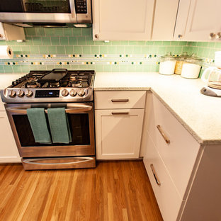 This is an example of a midcentury separate kitchen in Minneapolis with an undermount sink, shaker cabinets, white cabinets, recycled glass benchtops, green splashback, mosaic tile splashback, stainless steel appliances, medium hardwood floors, no island, brown floor and white benchtop.