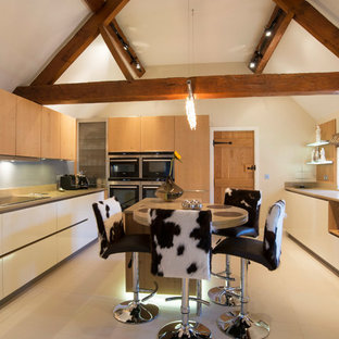 This is an example of a large rustic u-shaped kitchen in West Midlands with flat-panel cabinets, white cabinets, wood worktops, an island, beige floors, blue splashback and beige worktops.