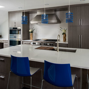 Photo of a large modern l-shaped eat-in kitchen in New York with an undermount sink, flat-panel cabinets, grey cabinets, quartzite benchtops, white splashback, porcelain splashback, stainless steel appliances, dark hardwood floors and with island.