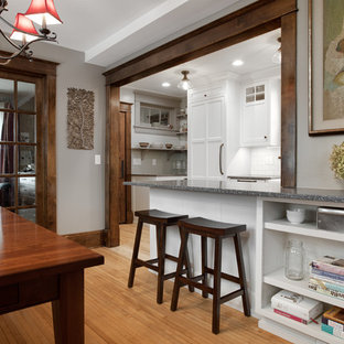 Design ideas for a mid-sized traditional u-shaped eat-in kitchen in Minneapolis with a farmhouse sink, shaker cabinets, white cabinets, recycled glass benchtops, white splashback, subway tile splashback, panelled appliances, light hardwood floors, a peninsula, brown floor and grey benchtop.