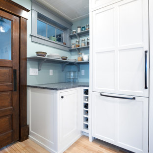 Inspiration for a mid-sized traditional u-shaped eat-in kitchen in Minneapolis with a farmhouse sink, shaker cabinets, white cabinets, recycled glass benchtops, white splashback, subway tile splashback, panelled appliances, light hardwood floors, a peninsula, brown floor and grey benchtop.