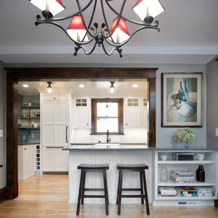 Photo of a mid-sized traditional u-shaped eat-in kitchen in Minneapolis with a farmhouse sink, shaker cabinets, white cabinets, recycled glass benchtops, white splashback, subway tile splashback, panelled appliances, light hardwood floors, a peninsula, brown floor and grey benchtop.