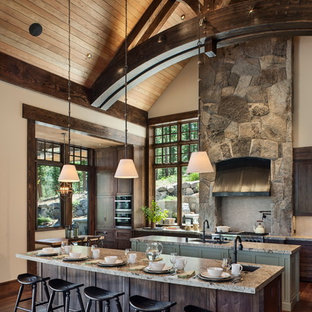 Design ideas for a large rustic open plan kitchen in Sacramento with a submerged sink, shaker cabinets, dark wood cabinets, grey splashback, stainless steel appliances, dark hardwood flooring, multiple islands, brown floors and granite worktops.