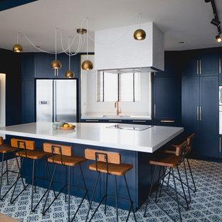 Foto de cocina tradicional renovada con fregadero de doble seno, armarios con paneles lisos, puertas de armario azules, electrodomésticos de acero inoxidable, una isla y suelo multicolor