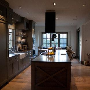 バンクーバーの中サイズのサンタフェスタイルのおしゃれなキッチン (エプロンフロントシンク、落し込みパネル扉のキャビネット、グレーのキャビネット、珪岩カウンター、シルバーの調理設備の、無垢フローリング) の写真