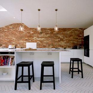 Imagen de cocina en L, contemporánea, con armarios con paneles lisos, puertas de armario blancas, encimera de mármol, salpicadero rojo, salpicadero de ladrillos, electrodomésticos negros, una isla y suelo blanco