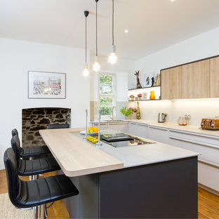 Photo of a medium sized contemporary l-shaped kitchen in Devon with a double-bowl sink, flat-panel cabinets, stainless steel appliances, light hardwood flooring, an island, brown floors and grey worktops.