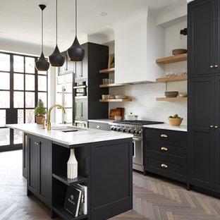 Klassische Küche mit Unterbauwaschbecken, Schrankfronten im Shaker-Stil, schwarzen Schränken, Küchenrückwand in Weiß, Rückwand aus Metrofliesen, Küchengeräten aus Edelstahl, dunklem Holzboden, Kücheninsel und braunem Boden in Toronto