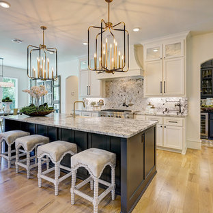 Transitional kitchen designs - Inspiration for a transitional l-shaped light wood floor and brown floor kitchen remodel in Oklahoma City with a farmhouse sink, recessed-panel cabinets, white cabinets, gray backsplash, stone slab backsplash, stainless steel appliances, an island and gray countertops