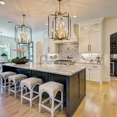 Inspiration for a transitional l-shaped light wood floor and brown floor kitchen remodel in Oklahoma City with a farmhouse sink, recessed-panel cabinets, white cabinets, gray backsplash, stone slab backsplash, stainless steel appliances, an island and gray countertops