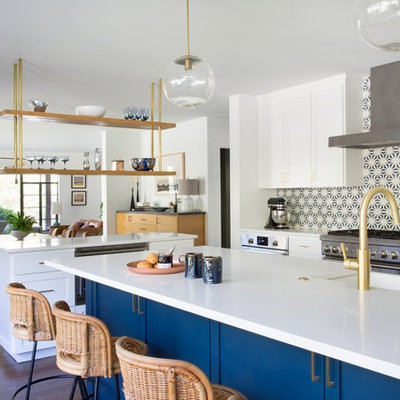 Open concept kitchen - eclectic dark wood floor and brown floor open concept kitchen idea in Austin with a farmhouse sink, shaker cabinets, blue cabinets, multicolored backsplash, mosaic tile backsplash, stainless steel appliances and two islands