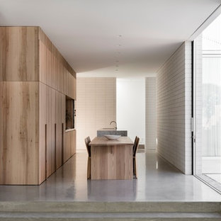 This is an example of a modern eat-in kitchen in Sydney with flat-panel cabinets, light wood cabinets, concrete floors, with island and grey floor.
