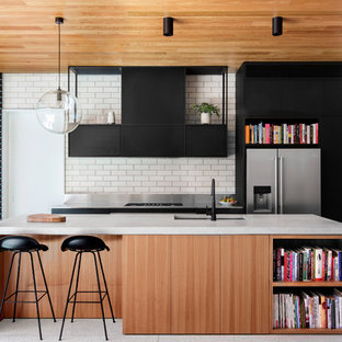 Inspiration for a contemporary galley kitchen in Sydney with an undermount sink, flat-panel cabinets, medium wood cabinets, concrete benchtops, grey splashback, brick splashback, stainless steel appliances, with island, grey floor and grey benchtop.
