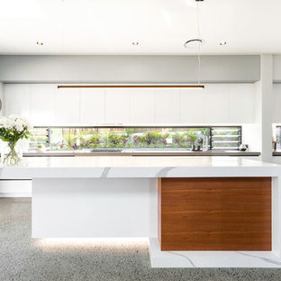 This is an example of a large contemporary galley open plan kitchen in Brisbane with flat-panel cabinets, white cabinets, window splashback, stainless steel appliances, with island, grey floor, white benchtop, a drop-in sink, quartz benchtops and concrete floors.