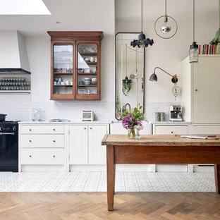 Eklektisk inredning av ett vit vitt parallellkök, med en rustik diskho, släta luckor, vita skåp, vitt stänkskydd, stänkskydd i tunnelbanekakel, svarta vitvaror, en köksö och flerfärgat golv