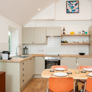 Modern l-shaped kitchen/diner in Wiltshire with a built-in sink, shaker cabinets, beige cabinets, wood worktops, white splashback, medium hardwood flooring, brown floors and brown worktops.