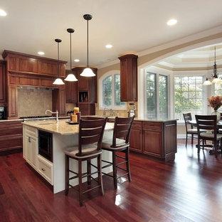 Geschlossene, Große Klassische Küche in L-Form mit Unterbauwaschbecken, profilierten Schrankfronten, dunklen Holzschränken, Granit-Arbeitsplatte, Küchenrückwand in Beige, Rückwand aus Travertin, Küchengeräten aus Edelstahl, dunklem Holzboden, Kücheninsel und braunem Boden in Kansas City