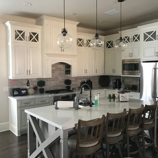 Mid-sized farmhouse open concept kitchen photos - Example of a mid-sized country l-shaped dark wood floor and brown floor open concept kitchen design in Austin with raised-panel cabinets, white cabinets, an island, terrazzo countertops, gray backsplash, stone tile backsplash, stainless steel appliances and a double-bowl sink