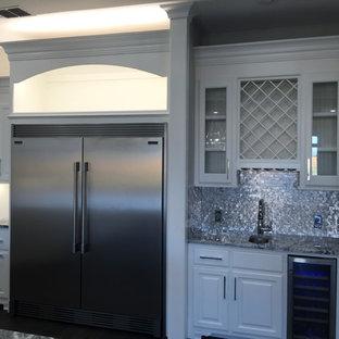 Offene, Mittelgroße Klassische Küche in L-Form mit Landhausspüle, profilierten Schrankfronten, weißen Schränken, Marmor-Arbeitsplatte, Küchenrückwand in Metallic, Rückwand aus Metallfliesen, Küchengeräten aus Edelstahl, dunklem Holzboden und Kücheninsel in Orange County