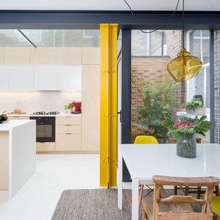 Idéer för små funkis linjära kök med öppen planlösning, med en integrerad diskho, släta luckor, skåp i ljust trä, vitt stänkskydd, stänkskydd i keramik, svarta vitvaror, betonggolv, en köksö och vitt golv