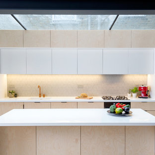 Diseño de cocina lineal, moderna, pequeña, cerrada, con fregadero integrado, armarios con paneles lisos, puertas de armario de madera clara, salpicadero de azulejos de cerámica, electrodomésticos negros, suelo de cemento, una isla y suelo turquesa