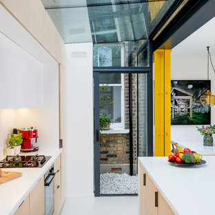 This is an example of a small modern single-wall open plan kitchen in London with an integrated sink, flat-panel cabinets, light wood cabinets, white splashback, ceramic splashback, black appliances, concrete floors, with island and white floor.