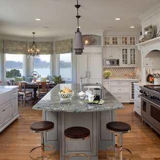 Example of a classic medium tone wood floor kitchen design in San Francisco with a farmhouse sink, shaker cabinets, granite countertops, ceramic backsplash, an island, paneled appliances and white cabinets