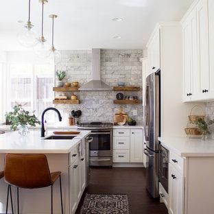 Foto på ett vintage l-kök, med en undermonterad diskho, skåp i shakerstil, vita skåp, bänkskiva i kvarts, grått stänkskydd, stänkskydd i marmor, rostfria vitvaror, laminatgolv, en köksö och brunt golv
