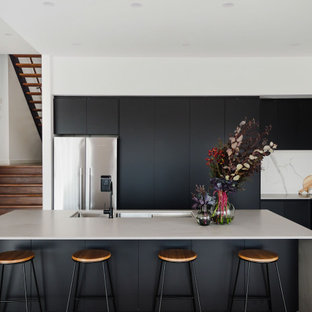 Inspiration for a contemporary l-shaped kitchen in Melbourne with a triple-bowl sink, flat-panel cabinets, black cabinets, multi-coloured splashback, stone slab splashback, stainless steel appliances, dark hardwood floors, with island, brown floor and grey benchtop.