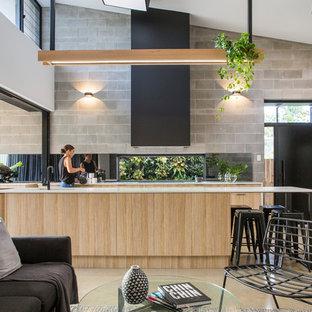 Новый формат декора квартиры: кухня-гостиная в современном стиле с плоскими фасадами, черными фасадами, серым фартуком, техникой из нержавеющей стали, бетонным полом и островом