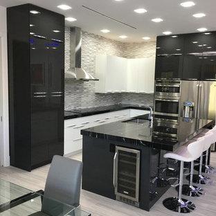 Cette photo montre une cuisine américaine moderne en L de taille moyenne avec un évier encastré, un placard à porte plane, des portes de placard noires, une crédence multicolore, un électroménager en acier inoxydable, un sol en contreplaqué, un îlot central, un sol beige et un plan de travail noir.