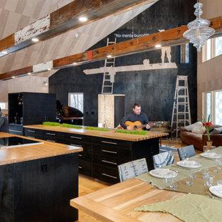 ボストンの広いモダンスタイルのおしゃれなキッチン (アンダーカウンターシンク、フラットパネル扉のキャビネット、黒いキャビネット、木材カウンター、シルバーの調理設備、合板フローリング) の写真