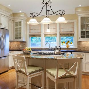 ボストンのヴィクトリアン調のおしゃれなキッチン (エプロンフロントシンク、落し込みパネル扉のキャビネット、白いキャビネット、ベージュキッチンパネル、ボーダータイルのキッチンパネル、シルバーの調理設備の、御影石カウンター、ベージュのキッチンカウンター) の写真