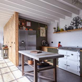 Пример оригинального дизайна: кухня в стиле кантри с зелеными фасадами, белым фартуком, фартуком из плитки кабанчик, белой техникой, островом, серым полом, балками на потолке, потолком из вагонки и сводчатым потолком