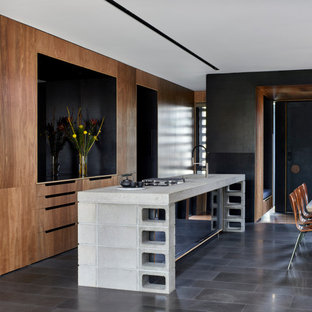 Mid-sized contemporary galley open plan kitchen in Melbourne with an undermount sink, recessed-panel cabinets, brown cabinets, concrete benchtops, white splashback, mirror splashback, panelled appliances, with island, grey floor, grey benchtop and recessed.