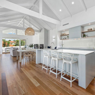 Mid-sized beach style galley open plan kitchen in Brisbane with an undermount sink, flat-panel cabinets, window splashback, black appliances, with island, brown floor, exposed beam, vaulted, grey cabinets, medium hardwood floors and white benchtop.