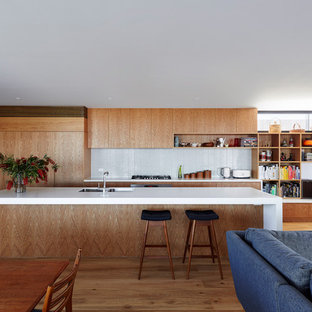 This is an example of a midcentury galley open plan kitchen in Los Angeles with a double-bowl sink, flat-panel cabinets, medium wood cabinets, white splashback, mosaic tile splashback, panelled appliances, medium hardwood floors, with island, brown floor and white benchtop.
