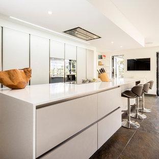 Imagen de cocina minimalista con armarios con paneles lisos, encimera de acrílico, suelo de pizarra, encimeras blancas, puertas de armario blancas, una isla y suelo marrón