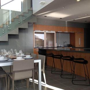 サンフランシスコの広いモダンスタイルのおしゃれなキッチン (フラットパネル扉のキャビネット、中間色木目調キャビネット、ドロップインシンク、クオーツストーンカウンター、グレーのキッチンパネル、ガラスタイルのキッチンパネル、シルバーの調理設備、セラミックタイルの床) の写真