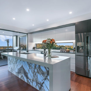 Large contemporary single-wall open plan kitchen in Brisbane with a double-bowl sink, flat-panel cabinets, white cabinets, black appliances, medium hardwood floors, brown floor, white benchtop, quartz benchtops, white splashback, glass sheet splashback and with island.